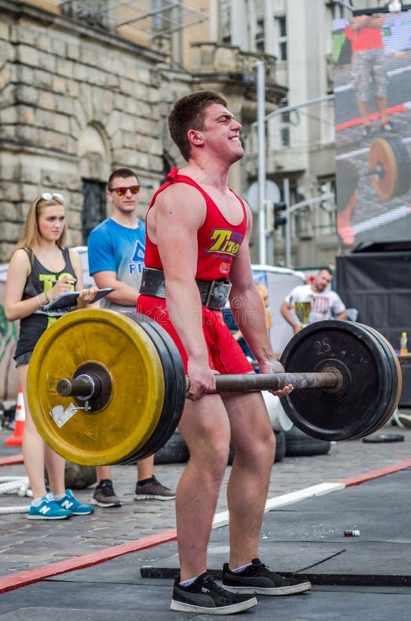 LVIV UKRAINA, CZERWIEC, - 2016: Silna bodybuilder atleta z pięknym ciałem nadymającym podnosić ciężkiego barbell na miasto ulicie zdjęcie royalty free