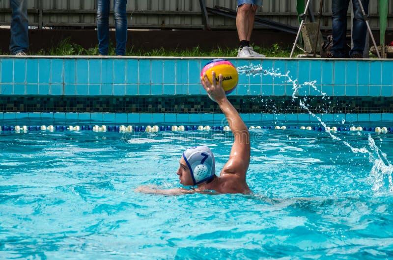 Lviv Ukraina - Juli 2015: Ukrainsk koppvattenpolo Idrottsman nenlagets bollen för polo för vatten i en simbassäng och gör att anf royaltyfri fotografi
