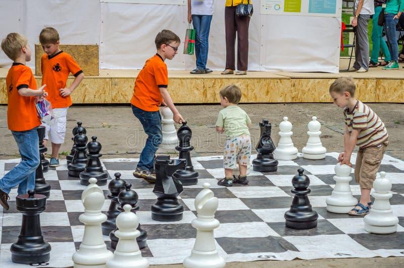 LVIV UKRAINA - JUNI 2016: Unga barn de framtida grandmastersna spelar på ett schack för schackbräde som utomhus övar enorma diagr arkivbild