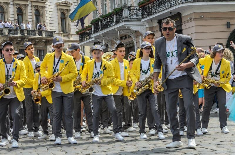 LVIV UKRAINA, MAJ, - 2018: Mosiężny zespół z trąbkami i saksofonami w karnawałowych kostiumach z żółtymi kurtkami chodzi wzdłuż obraz royalty free