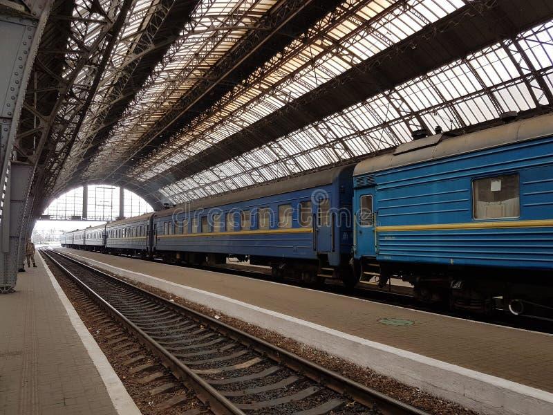 Lviv Ukraina - oktober 10 2017: Ställningarna för passageraredrev på en perforerad järnvägsstation under en metallbåge som göras  arkivfoto