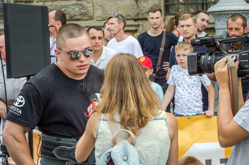 LVIV UKRAINA, SIERPIEŃ, - 2015: Siłacza ` s silna atleta wziąć TV przepytującym zdjęcie stock