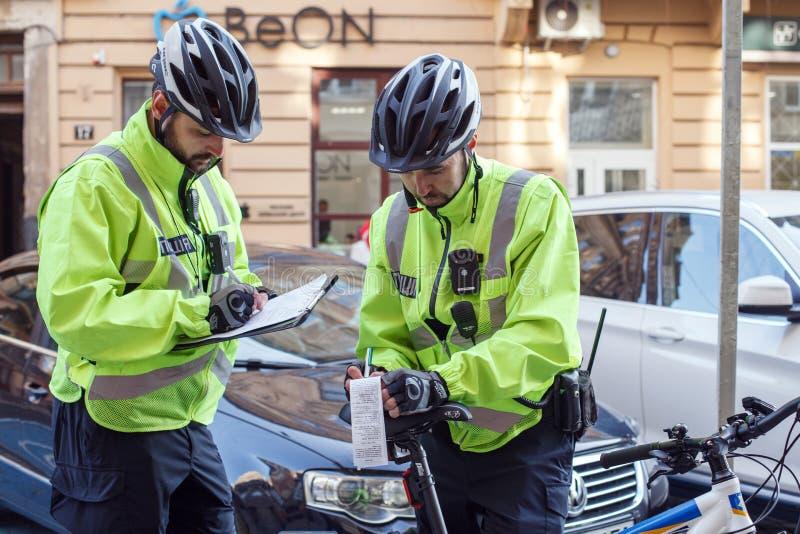 Lviv Ukraina 06 11 2018 Två poliser i cykelhjälmar Polispatrull med cyklar Polisen utfärdar böter arkivbilder
