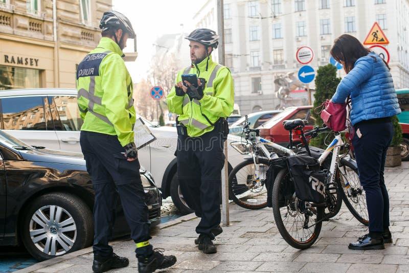 Lviv Ukraina 06 11 2018 Två poliser i cykelhjälmar Polispatrull med cyklar Polisen utfärdar böter fotografering för bildbyråer