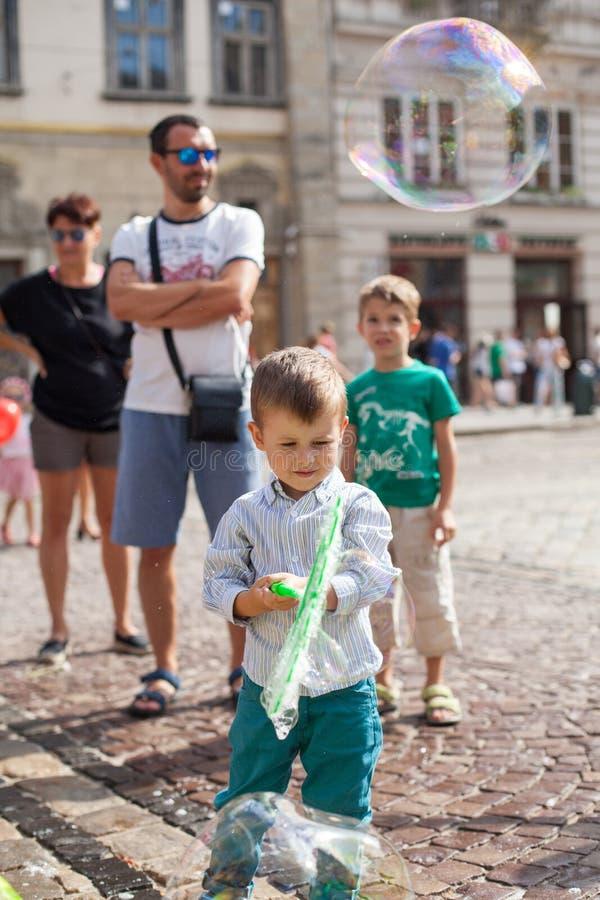 Lviv, Ukraine - 12 août 2018 : Petit garçon heureux jouant avec des bulles de savon sur la place principale de Lviv photos libres de droits