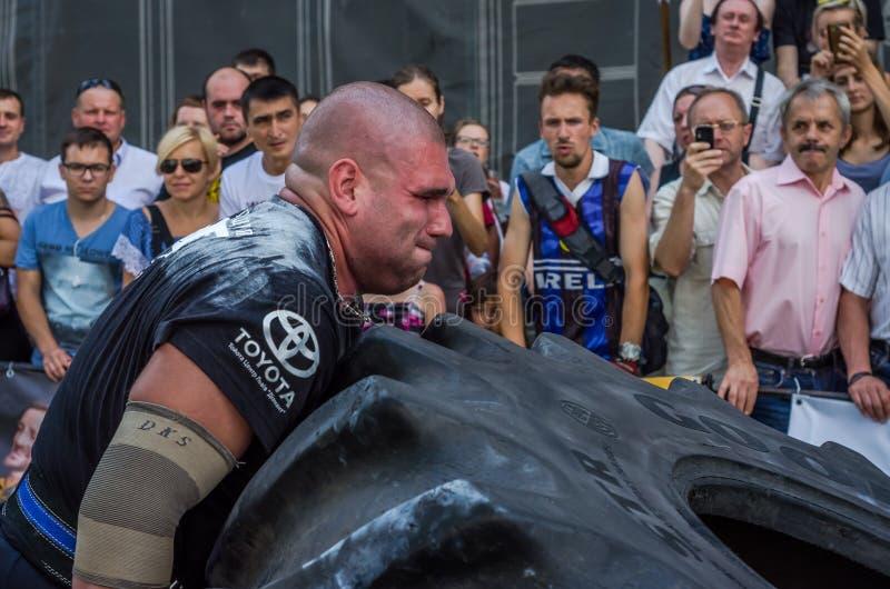 LVIV, UKRAINE - AOÛT 2017 : Un athlète fort superbe soulève une bonne roue énorme d'année aux concours devant le spectat enthousi photographie stock