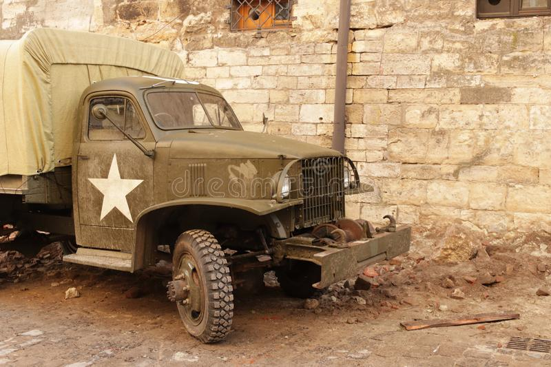Lviv, Ukraine - 9 9 2019: Army american cars on a street destroyed by war. Scenery for the Holocaust feature film during. World War II. Hot spots of military stock image