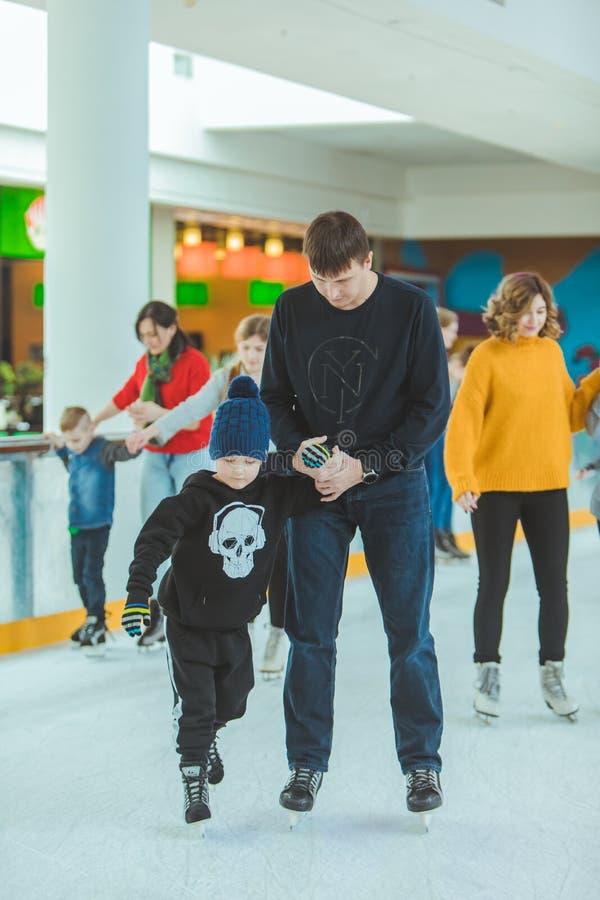 LVIV, UKRAINE - 3 f?vrier 2019 : fils de enseignement de p?re comment patiner sur la piste de ski photo stock