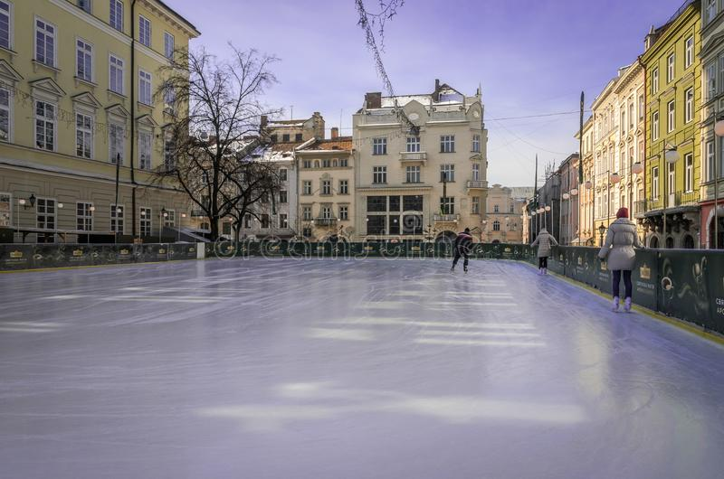 LVIV, UKRAINE - FEBRUARY 2018: Ice skating rink with skaters in a sunny afternoon in the center of Lviv, Ukraine stock photography
