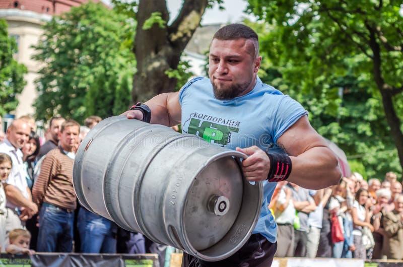 LVIV, UKRAINE - JUIN 2016 : L'homme fort de bodybuilder d'athlète avec le corps fort a un énorme baril en métal avec de la bière photo libre de droits