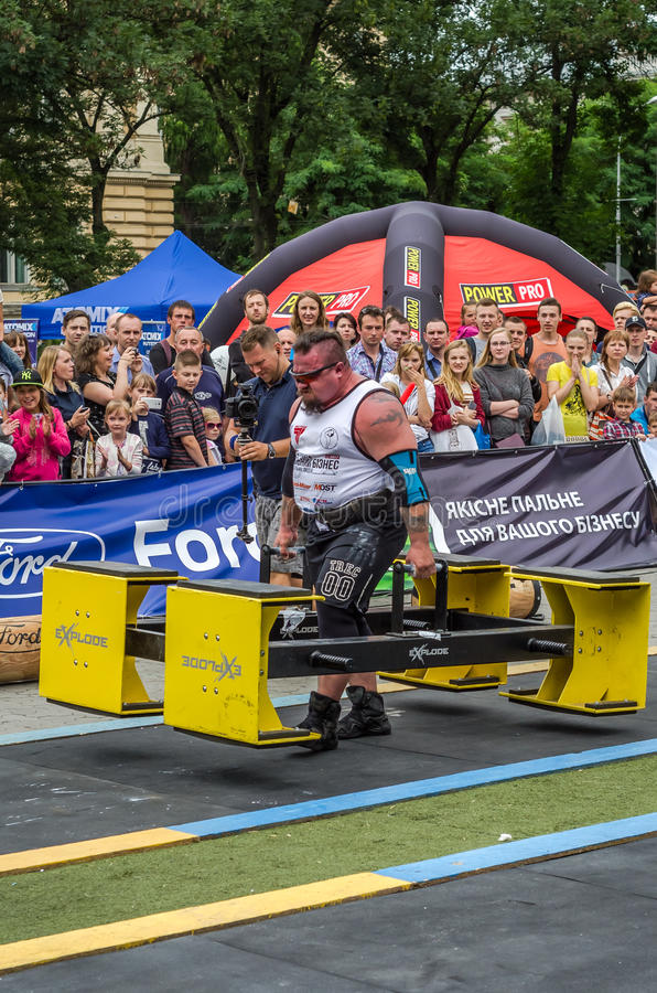 LVIV, UKRAINE - JULY 2016: Strong athlete bodybuilder strongman carries heavy metal design competitions World Strongest Team. Strong athlete bodybuilder stock image
