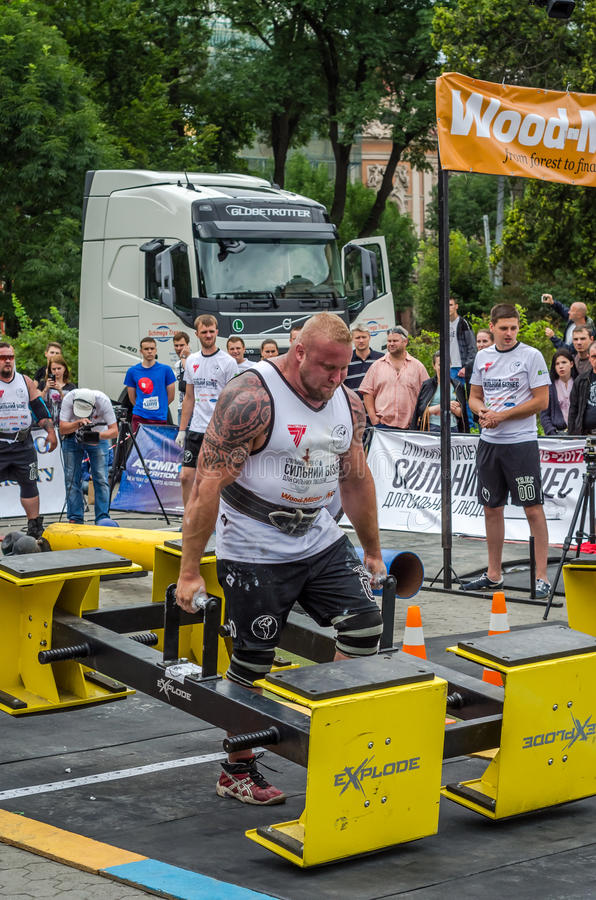 LVIV, UKRAINE - JULY 2016: Strong athlete bodybuilder strongman carries heavy metal design competitions World Strongest Team. Strong athlete bodybuilder royalty free stock photo