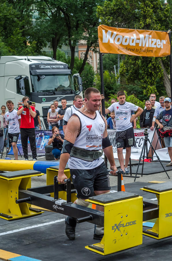 LVIV, UKRAINE - JULY 2016: Strong athlete bodybuilder strongman carries heavy metal design competitions World Strongest Team. Strong athlete bodybuilder stock photos