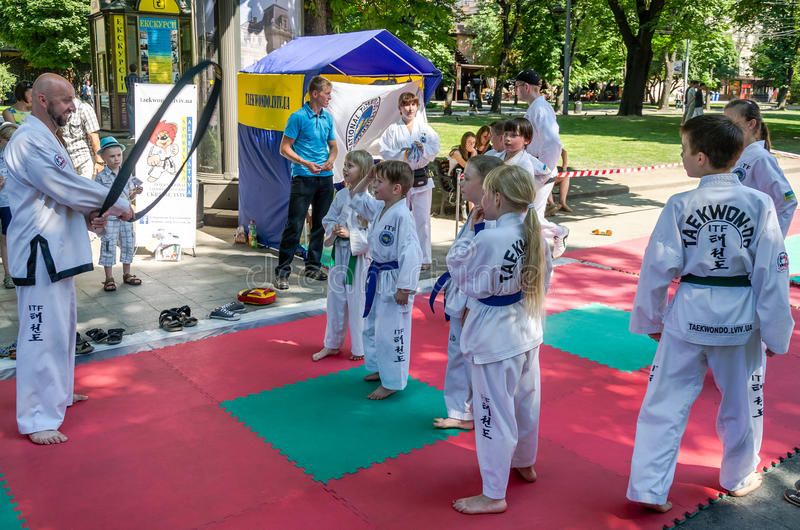 Lviv, Ukraine - July 2015: Yarych street Fest 2015. Demonstration exercise outdoors in the park children and their teacher royalty free stock photo