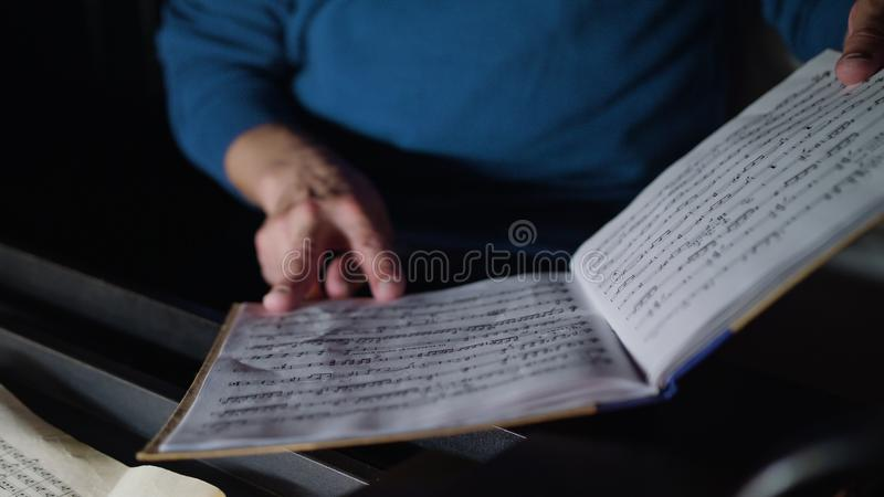 Conductor in an Orchestra Pit Studies Sheet Music. Lviv, Ukraine - June, 2017: Close up hands of mid aged conductor alone in dark orchestra pit studies sheet stock images