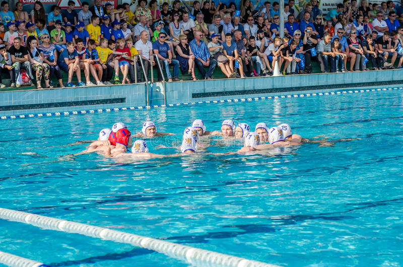 LVIV, UKRAINE - JUNE 2016: Men's water polo team is tuned to the game in the pool shouting their battle cry stock image