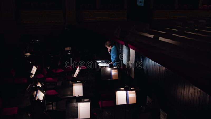 Conductor in an Orchestra Pit Studies Sheet Music. Lviv, Ukraine - June, 2017: Mid aged conductor alone in dark orchestra pit studies sheet music and tweets the stock photos