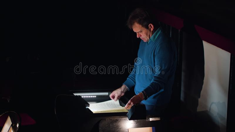 Conductor in an Orchestra Pit Studies Sheet Music. Lviv, Ukraine - June, 2017: Mid aged conductor alone in dark orchestra pit studies sheet music and tweets the royalty free stock photography