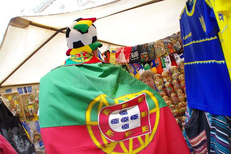 LVIV, UKRAINE - JUNE 9, 2012: Portugal football fans Euro-2012. LVIV, UKRAINE - JUNE 9, 2012: Portugal football fans buy souvenirs in the center of the Lviv city stock image