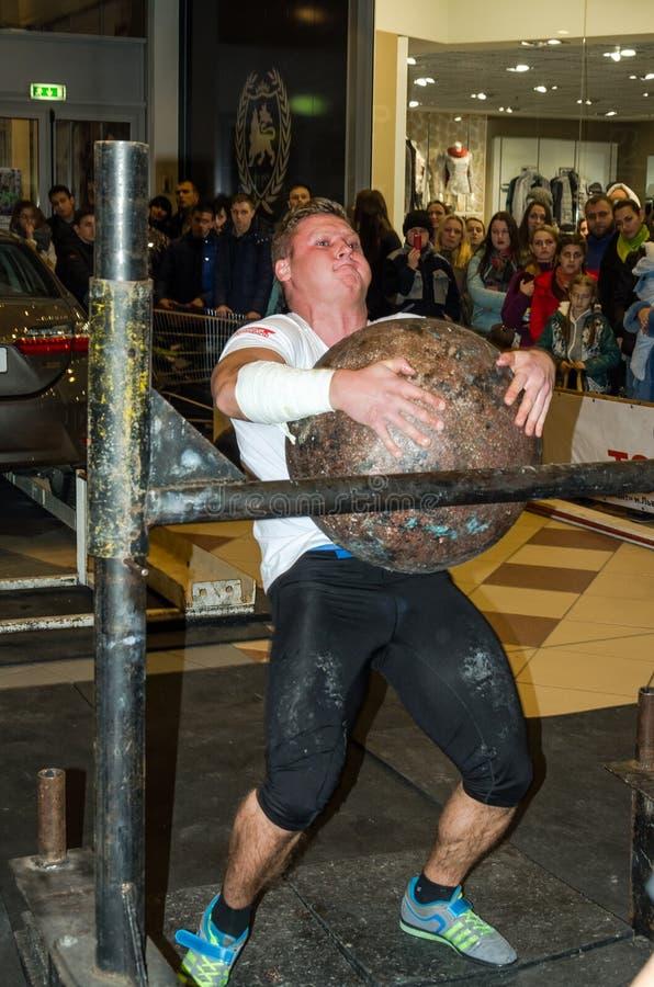 LVIV, UKRAINE - NOVEMBER 2016: Strong athlete strongman lifts a heavy stone ball. Strong athlete strongman lifts a heavy stone ball royalty free stock photos