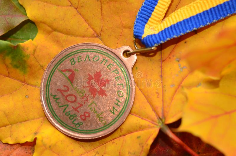 Lviv/Ukraine - October 7 2018: Medal from autumn Kid`s bicycle race in Lviv. Yellow maple leaves us a background. Medal for participation royalty free stock image