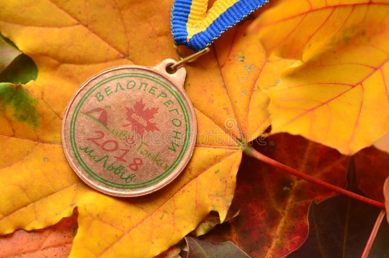 Lviv/Ukraine - October 7 2018: Medal from autumn Kid`s bicycle race in Lviv. Yellow maple leaves us a background. Medal for participation royalty free stock photography