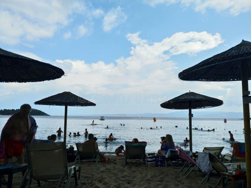 lWicker plażowi parasole pod niebieskim niebem z chmurami, Halkidiki Grecja obraz royalty free