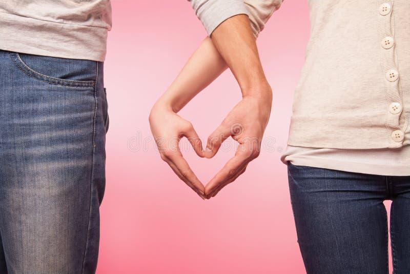 Lwoman e mani dell'uomo che mostrano forma del cuore fotografie stock libere da diritti