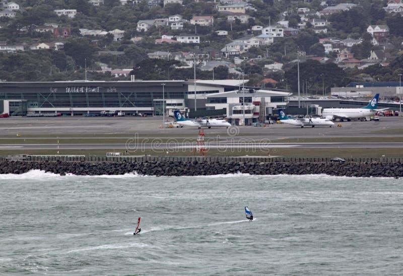 Lyall海湾的两位风冲浪者在惠灵顿新西兰在一灰色风暴日 机场在背景中能被看见 库存照片