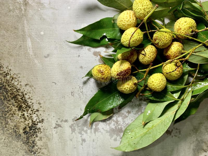 Lychees with green leaves and drops of water on a rustic background, Food photography. Fresh lychees with green leaves and drops of water on a rustic background stock image
