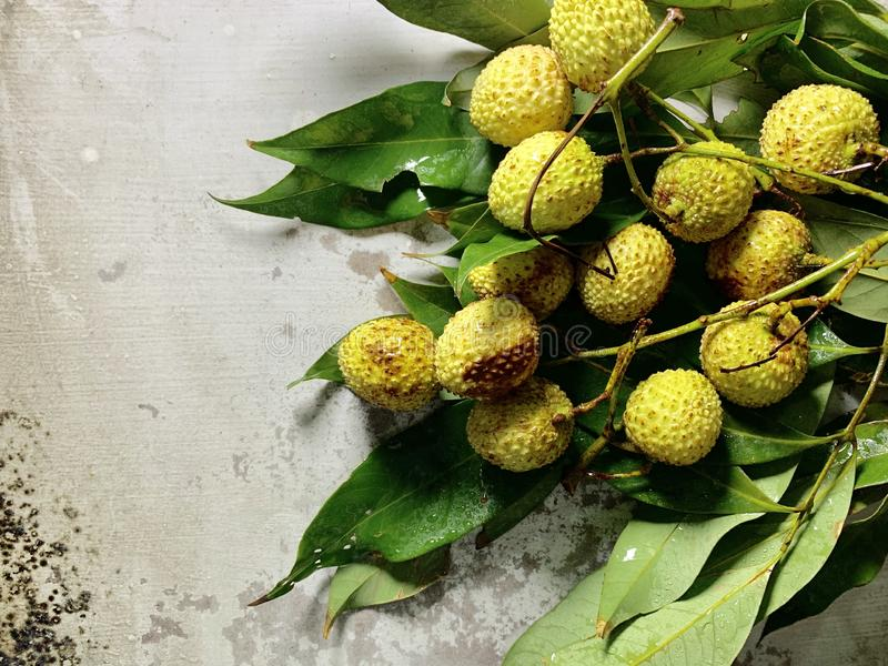 Lychees with green leaves isolated on a rustic background, Food photography. Fresh lychees with green leaves isolated on a rustic background, Food photography stock photo