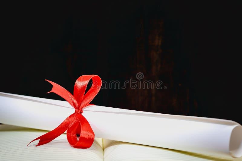 Lyckönskan för att avlägga examen akademikermössan och avläggandet av examen bläddrar, bundet med det röda bandet, på en bunt av  royaltyfri bild