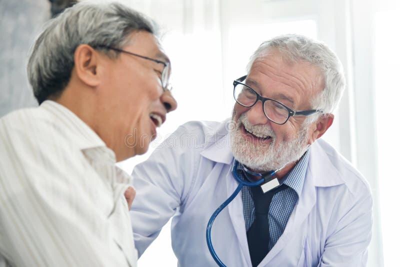 Lycka av den höga manliga doktorn med den asiatiska manliga patienten fotografering för bildbyråer