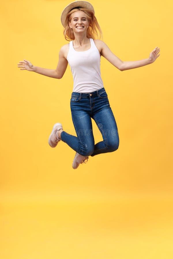 Lycka dröm, gyckel, glädje, sommarbegrepp Mycket den tonåriga upphetsade lyckliga gulliga caucasianen hoppar upp, i sommardräkt,  royaltyfri bild
