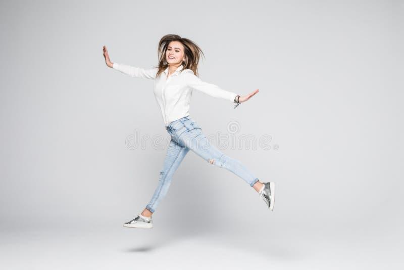 Lycka, frihet, makt, rörelse och folkbegrepp - le banhoppning för ung kvinna i luft med lyftta nävar över vit bakgrund arkivfoton