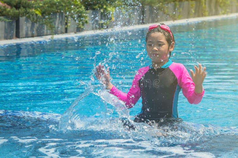 Lycka och att le den asiatiska gulliga lilla flickan har rolig k?nsla och tycker om i simbass?ng royaltyfria foton