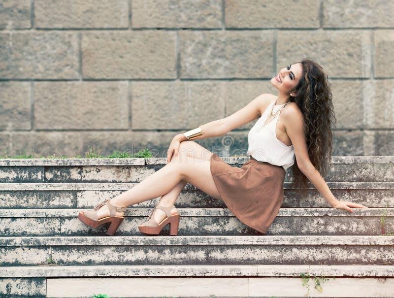 Lycka och skönhet Le sammanträde för ung kvinna på moment arkivfoton
