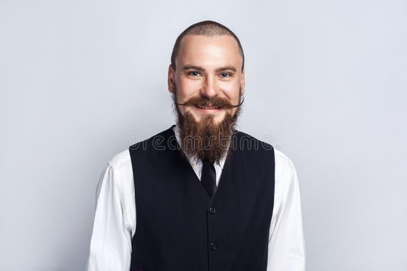 Lycka Stilig affärsman med skägg- och styremustaschen som ser kameran med den toothy smileyframsidan royaltyfria foton