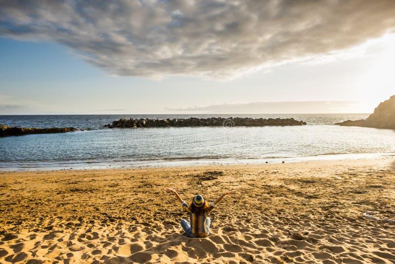 Lyckabegrepp med backview av den unga kvinnan som sitter på stranden och framme kramar havet och naturen av henne Frihet arkivbild