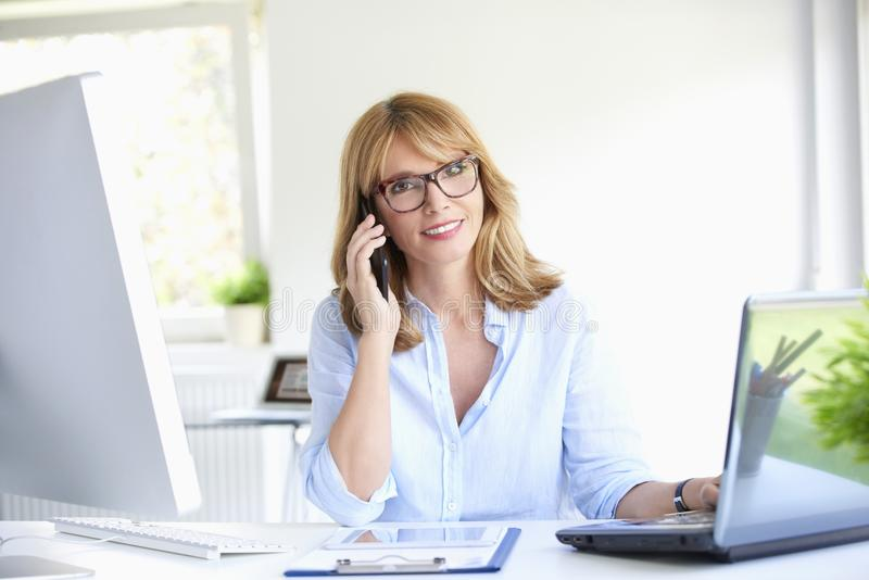 Lyckad affärskvinna som använder hennes mobiltelefon på kontoret royaltyfri foto