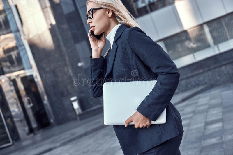 Lyckad affärskvinna som arbetar på bärbara datorn i stad arkivbild