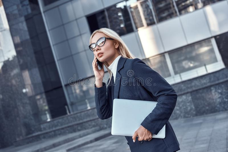 Lyckad affärskvinna som arbetar på bärbara datorn i stad royaltyfria foton