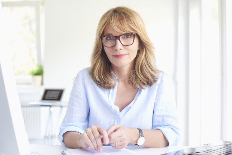 Lyckad affärskvinna som arbetar på det moderna kontoret royaltyfri bild