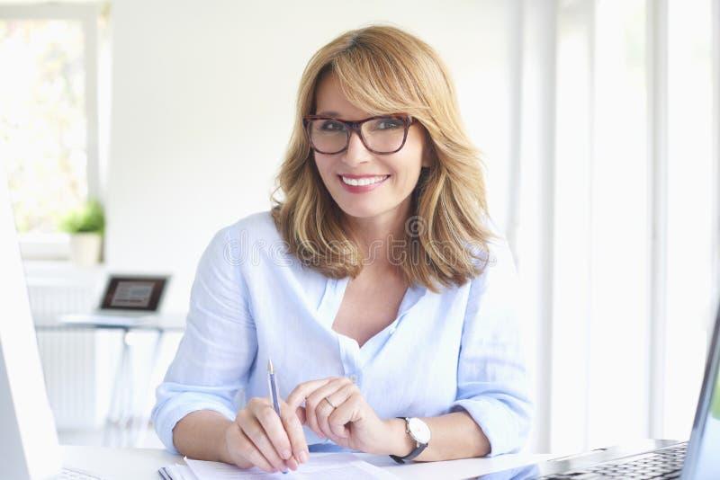 Lyckad affärskvinna som arbetar på det moderna kontoret royaltyfri fotografi
