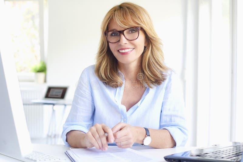 Lyckad affärskvinna som arbetar på det moderna kontoret arkivfoto