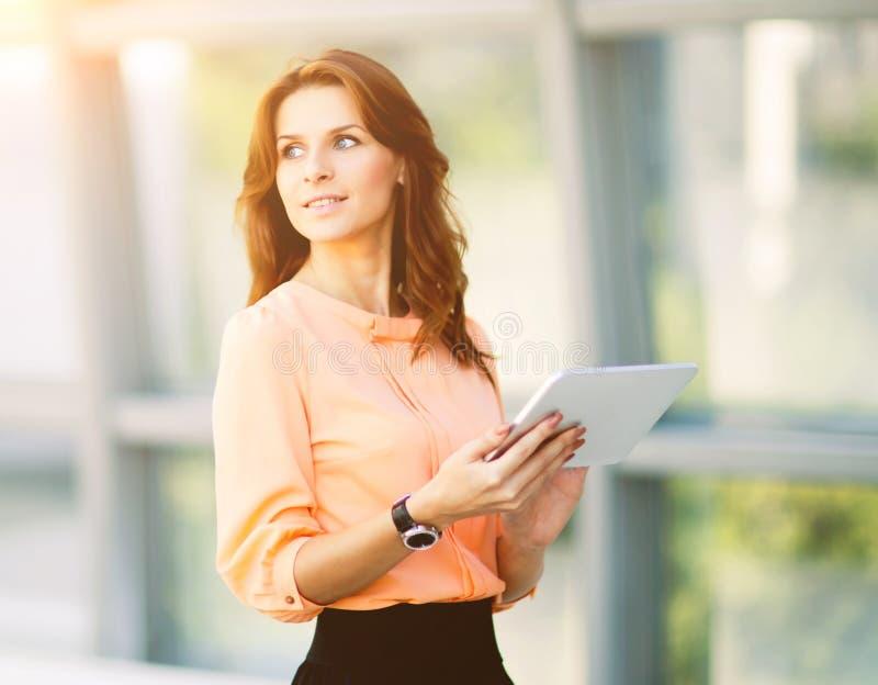 Lyckad affärskvinna som rymmer en digital minnestavladator i kontoret royaltyfri bild