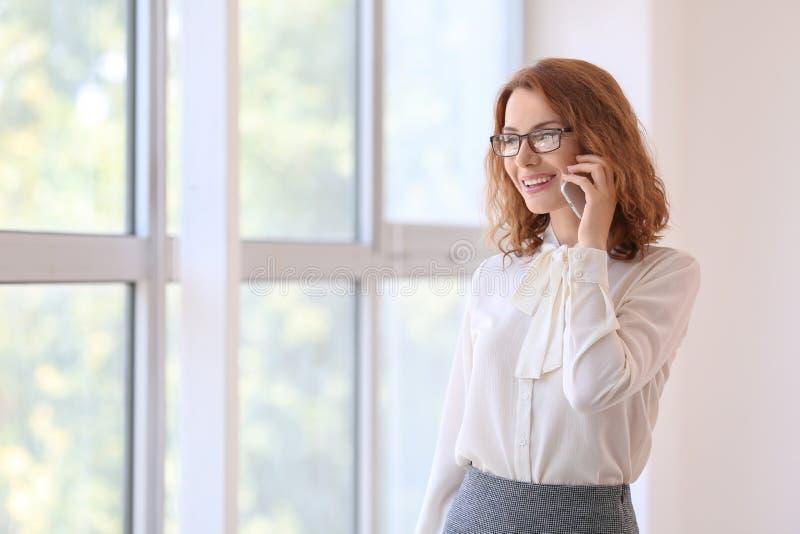 Lyckad affärskvinna som talar vid mobiltelefonen, medan stå nära fönster i regeringsställning royaltyfri bild