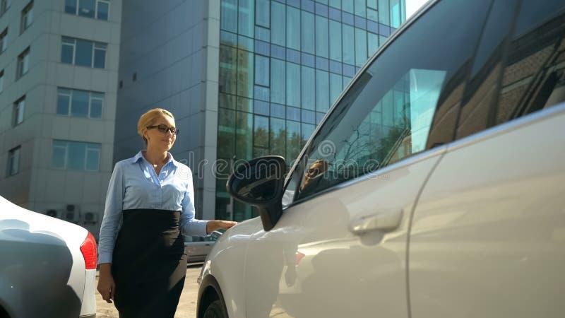 Lyckad affärskvinna som väljer bilen på automatisksalongen, köp, billån arkivbilder