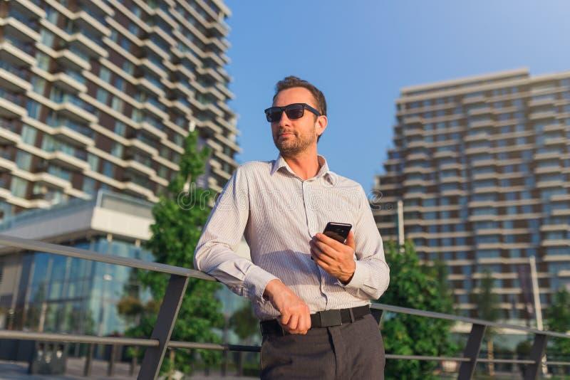 Lyckad affärsledare som utomhus använder smartphonen Kontorsbyggnader i bakgrunden arkivbilder