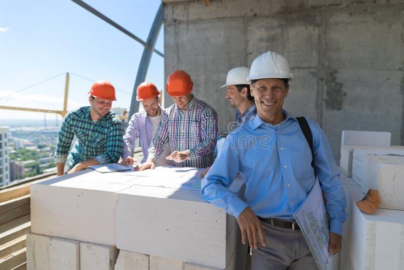 Lyckad affärsman över det Team Of Builders Discussing Blueprint planet efter möte av teknikerer på konstruktionsplats royaltyfri foto